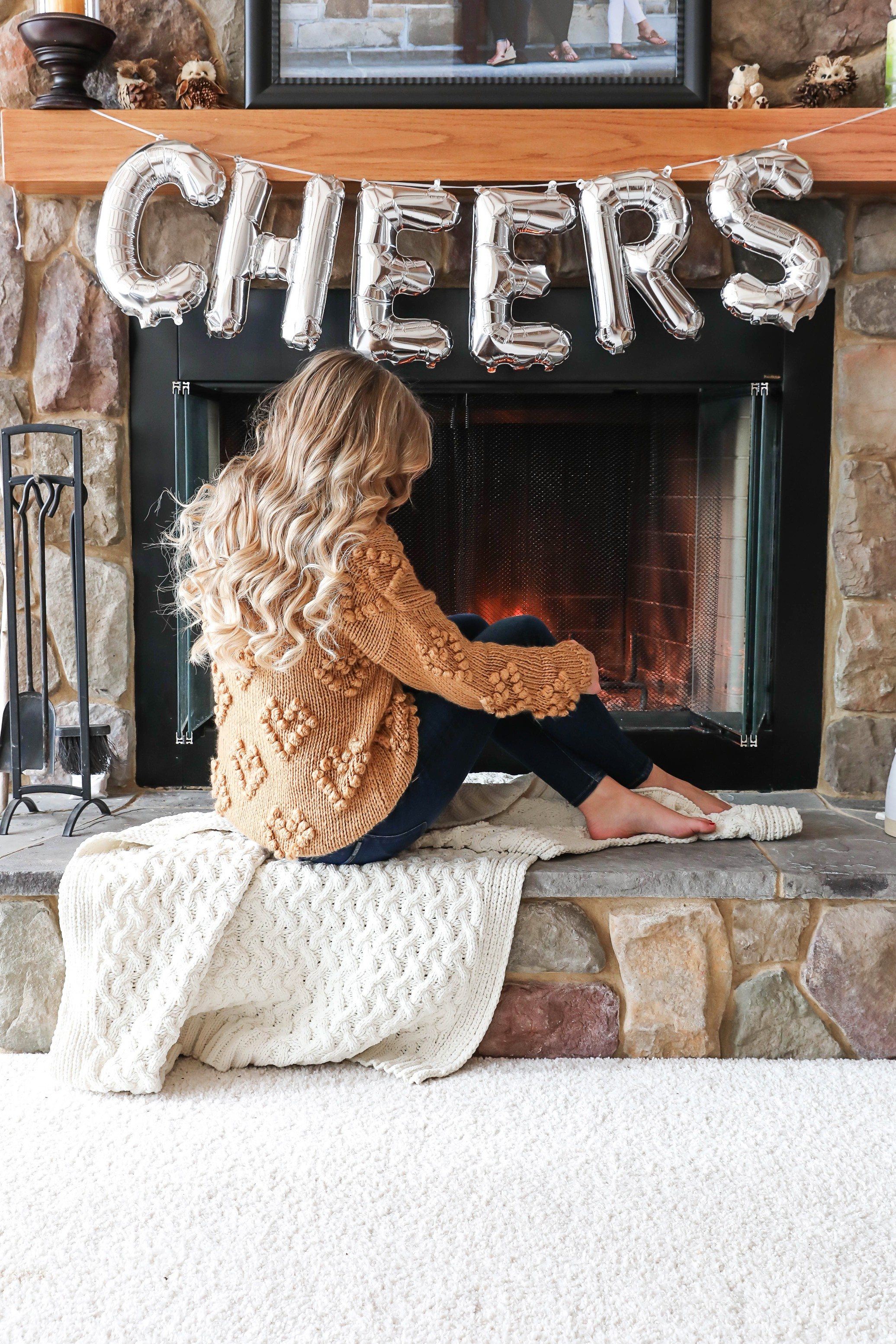 "Happy New Year! The cutest photoshoot with ""cheers"" balloons! New Year's Eve photoshoot next to a cozy fireplace! I also list out all my resolutions for the year! My cute Pomeranian pup is featured in some of the photos! Details on fashion blog daily dose of charm by lauren lindmark"