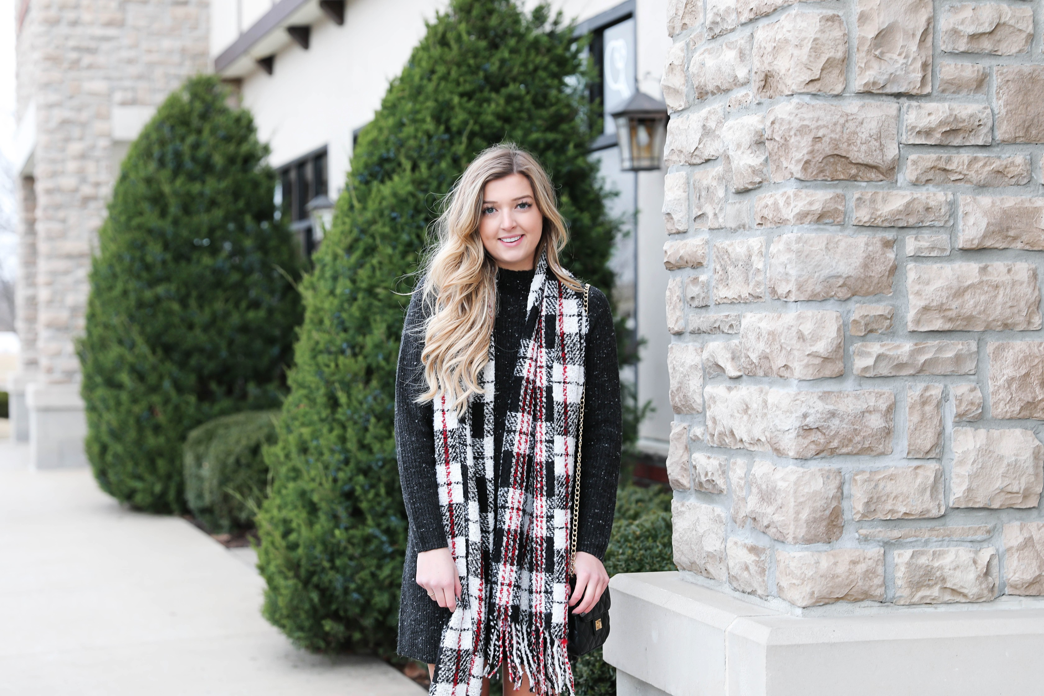 Black sweater dress paired with the cutest red plaid scarf and my favorite black over the knee boots! Cutest curly hair and winter outfit! Details on fashion blog daily dose of charm by lauren lindmark