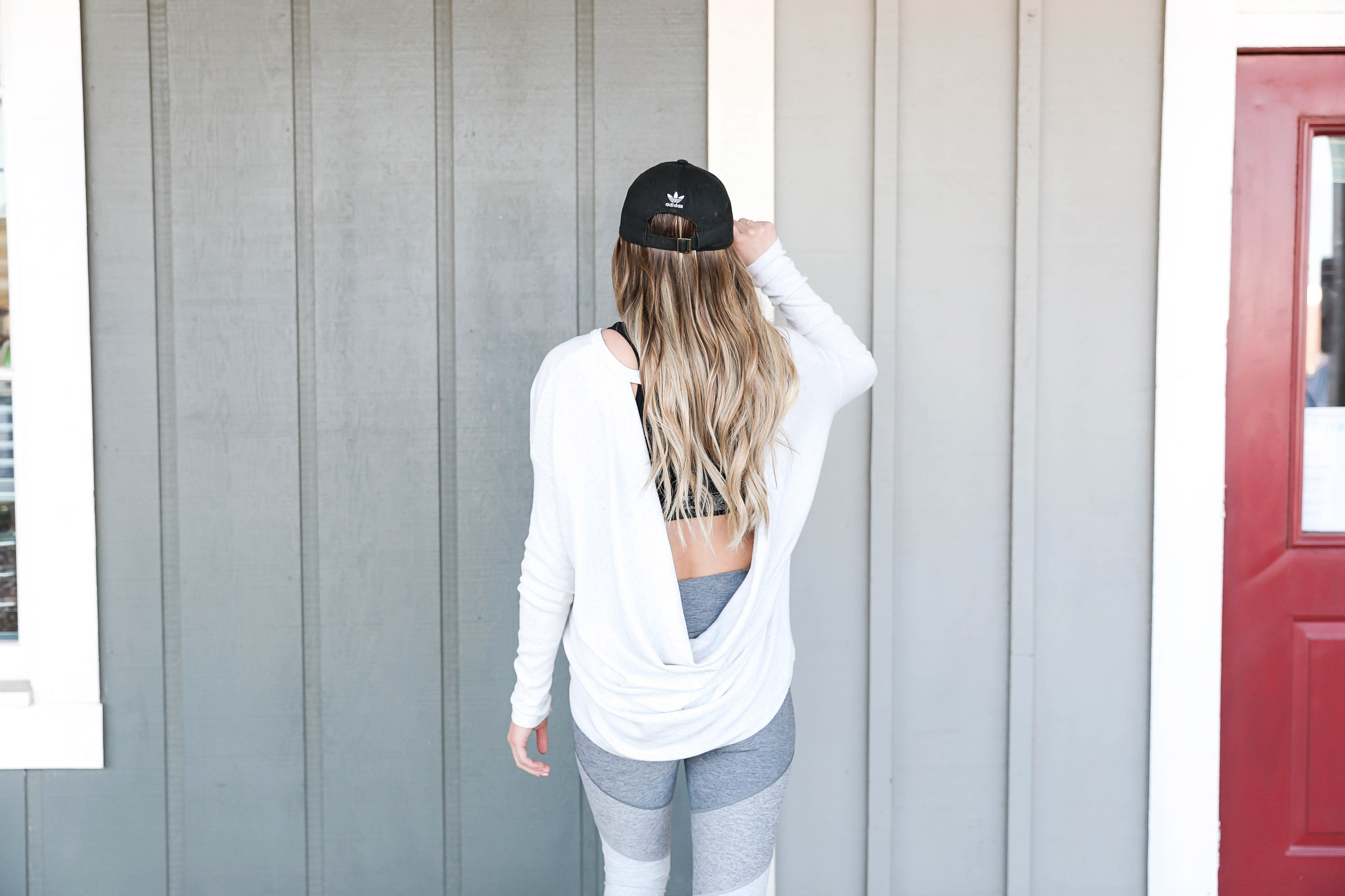 Cute New Year workout outfits for resolution inspiration in 2019! Stick to your fitness goals with a little outfit motivation! I love these color block leggings paired with the open back top and Adidas hat! Details on fashion blog daily dose of charm by lauren lindmark