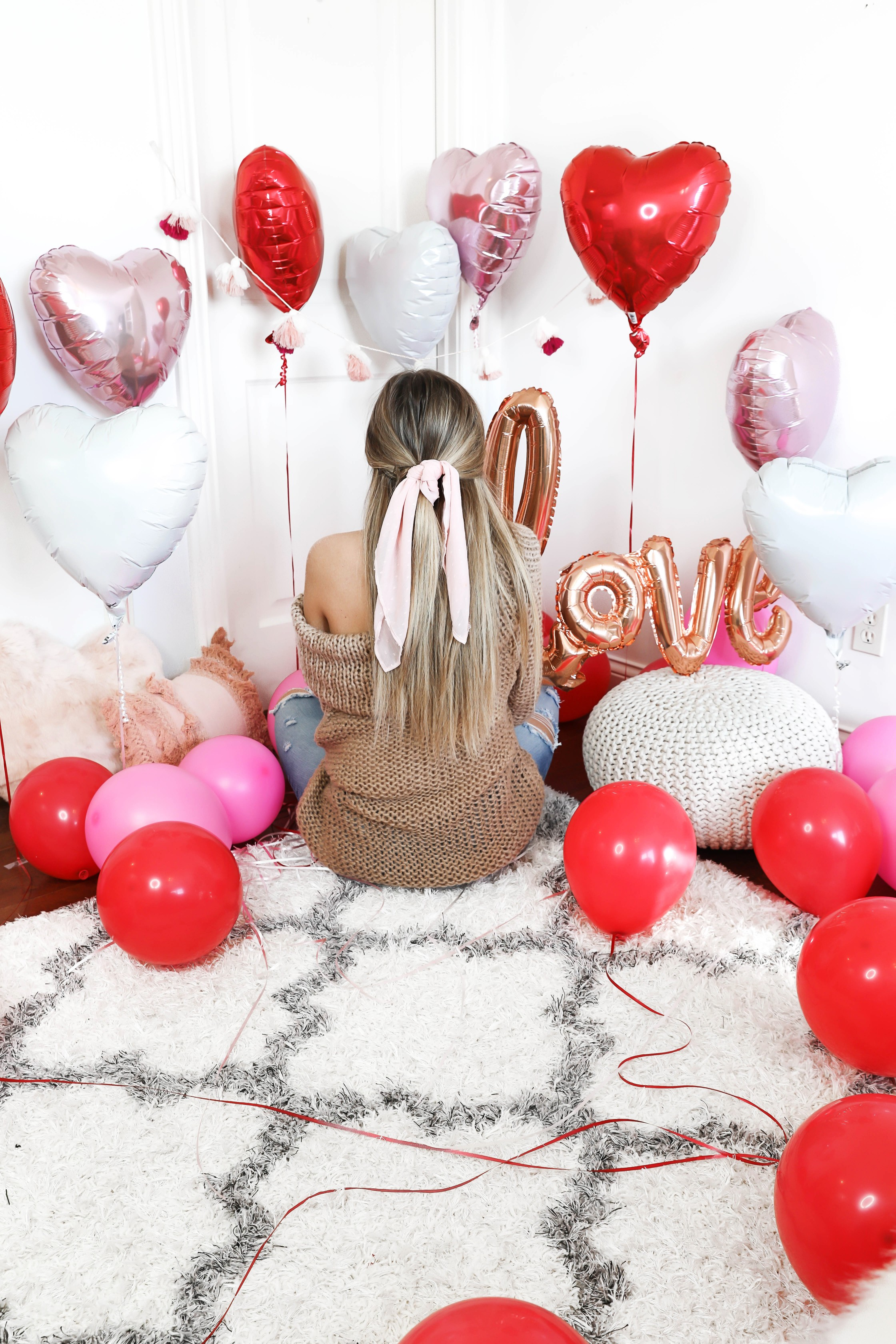 Valentine's Day shoot with the cutest heart shaped balloons and pink and red decor! My cute little pomeranian puppy dog made an appearance in the pics! I am wearing the cutest, tan, off the shoulder sweater from amazon and the cutest ripped denim from Red Dress Boutique! Details on style and fashion blog daily dose of charm by lauren lindmark